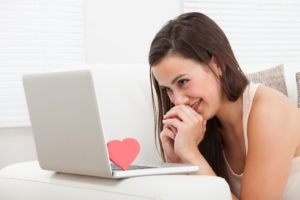 Side view of beautiful young woman dating online on laptop at home