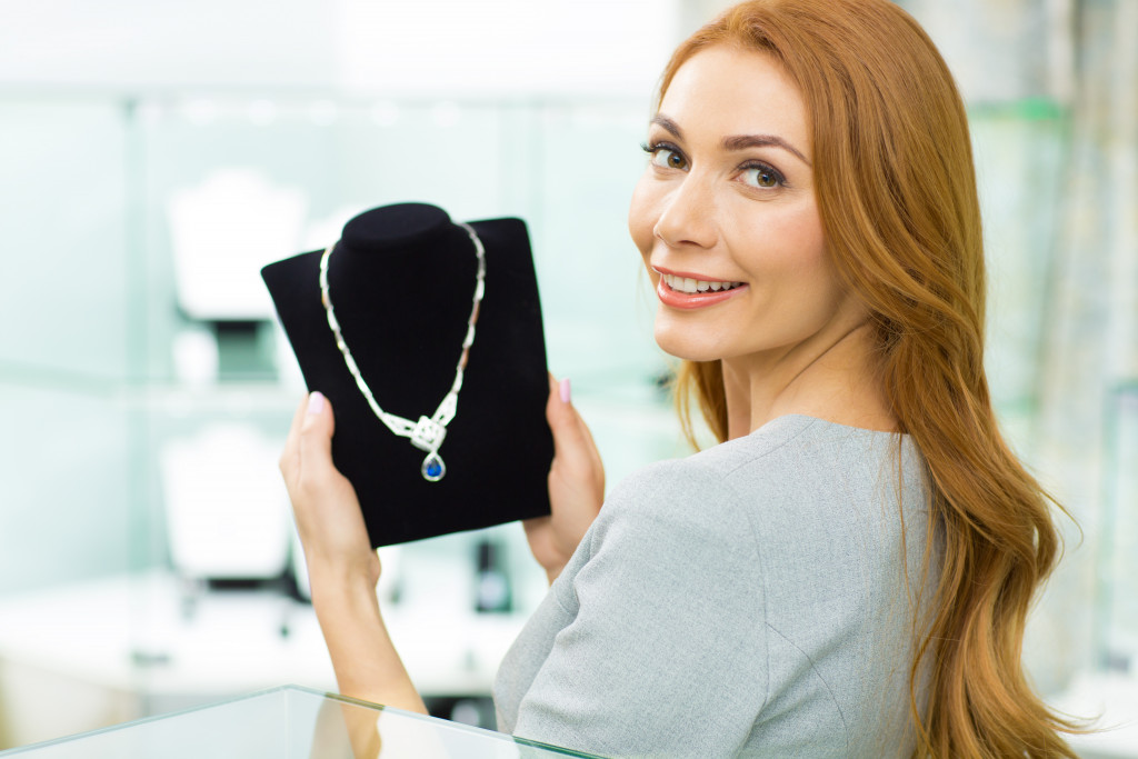 Gorgeous happy woman smiling to the camera over her shoulder holding beautiful diamond necklace choosing jewelry at the store consumptions retail money consumerism customer client elegance.