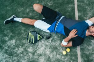 man laying down on a tennis court