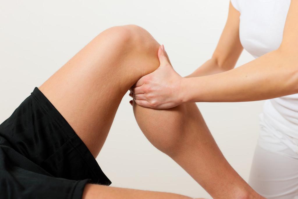 therapist checking on man's leg